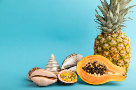 Ripe cut papaya, pineapple, passion fruit, seashells on blue pastel background. Side view, copy space. Tropical, healthy food, vacation, holidays concept.