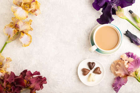 Cup of cioffee with chocolate candies and purple and burgundy iris flowers on gray concrete background. top view, flat lay, copy space, still life. Breakfast, morning, spring concept. Zdjęcie Seryjne