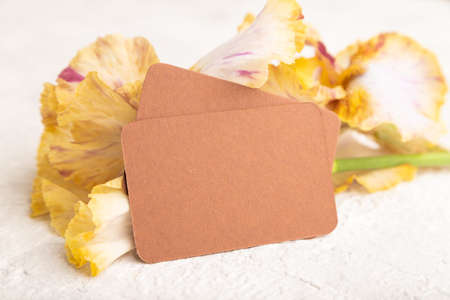 Brown business card with iris yellow flowers on white concrete background. side view, copy space, mockup, template, spring, summer minimalism concept. Zdjęcie Seryjne