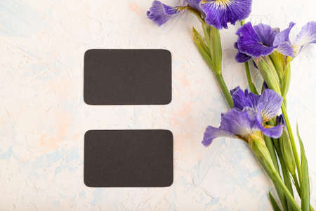 Black business card with blue iris flowers on white concrete background. top view, flat lay, copy space, still life. Breakfast, morning, spring concept. Zdjęcie Seryjne