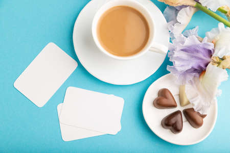 White business card with cup of cioffee, chocolate candies and iris flowers on blue pastel background. top view, flat lay, copy space, still life. Breakfast, morning, spring concept.