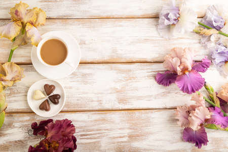 Cup of cioffee with chocolate candies, lilac and purple iris flowers on white wooden background. top view, flat lay, copy space, still life. Breakfast, morning, spring concept.