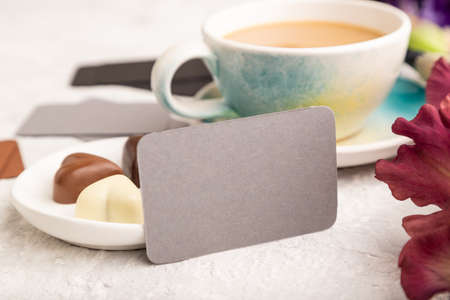 Gray business card with cup of cioffee, chocolate candies and iris flowers on gray concrete background. side view, copy space, still life. Breakfast, morning, spring concept.