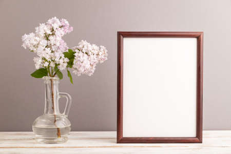 Wooden frame with lilac flower in glass on gray pastel background. side view, copy space, mockup, template, spring, summer minimalism concept. Zdjęcie Seryjne