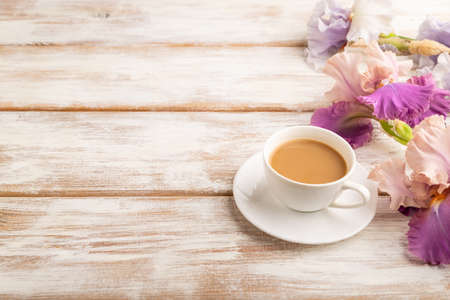Cup of cioffee with lilac and purple iris flowers on white wooden background. side view, copy space, still life. Breakfast, morning, spring concept. Zdjęcie Seryjne