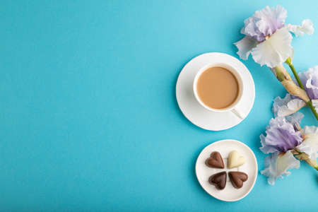 Cup of cioffee with chocolate candies and lilac iris flowers on blue pastel background. top view, flat lay, copy space, still life. Breakfast, morning, spring concept.