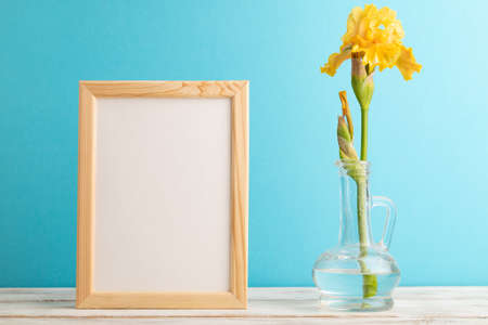 Wooden frame with yellow iris flower in glass on blue pastel background. side view, copy space, mockup, template, spring, summer minimalism concept.