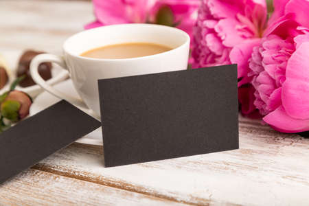 Black business card with pink peony flowers and cup of coffee on white wooden background. side view, copy space, still life. Breakfast, morning, spring concept.