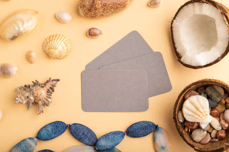 Brown paper business card with coconut, seashells, pebbles, beads on orange pastel background. Top view, flat lay, copy space. Tropical, healthy food, vacation, holidays concept.