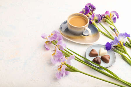 Cup of cioffee with chocolate candies and lilac iris flowers on white concrete background. side view, copy space, still life. Breakfast, morning, spring concept.
