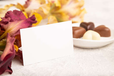White business card with chocolate candies and iris flowers on gray concrete background. side view, copy space, still life. Breakfast, morning, spring concept.
