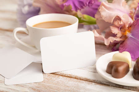 White business card with cup of cioffee, chocolate candies and iris flowers on white wooden background. side view, copy space, still life. Breakfast, morning, spring concept.