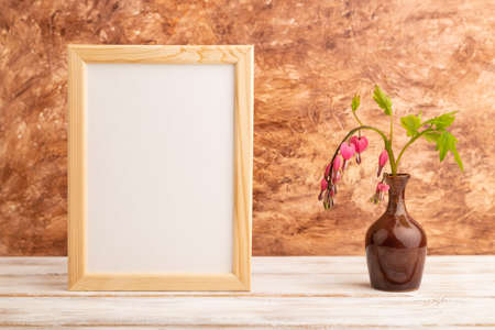 Wooden frame with pink dicentra, broken heart in ceramic vase on brown concrete background. side view, copy space, mockup, template, spring, summer minimalism concept.