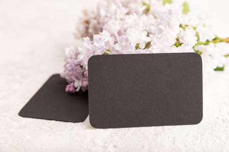 Black business card with lilac flowers on gray concrete background. side view, copy space, mockup, template, spring, summer minimalism concept.