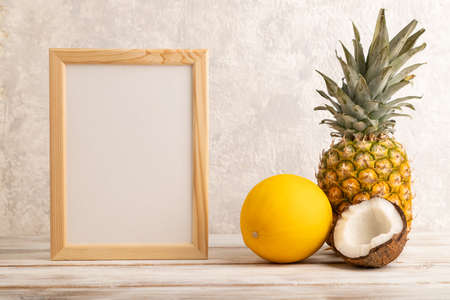 Wooden frame with pineapple, melon, coconut on gray concrete background. Side view, copy space. Tropical, healthy food, vacation, holidays concept.