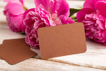 Brown business card with pink peony flowers on white wooden background. side view, copy space, still life. Breakfast, morning, spring concept.