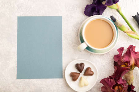 Blue paper sheet with cup of cioffee, chocolate candies, purple and burgundy iris flowers on gray concrete background. top view, flat lay, copy space, still life. Breakfast, morning, spring concept. Zdjęcie Seryjne