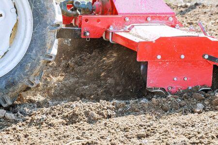 Farmer plowing the field. Tractor with a plow in a farm field.
