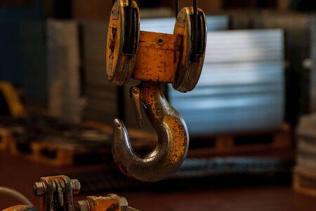 Closeup of yellow crane hook in a factory