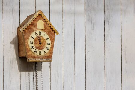 Old clock on a wooden light wall. Copy-space.
