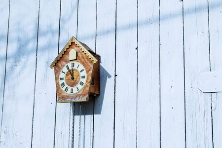 Old clock on a wooden light wall.