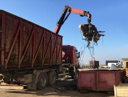 A grapple truck loads scrap industrial metal for recycling Stock Photo