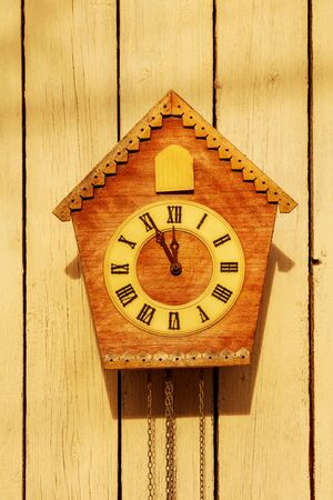 Old clock on a wooden light wall. Stock Photo