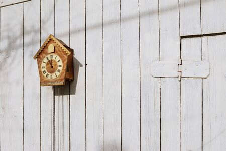 Old clock on a wooden light wall. Vintage clock. Cuckoo clock Banque d'images - 142153282