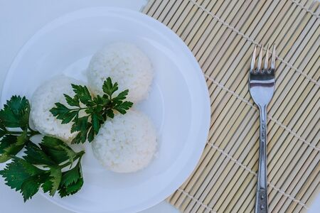 boiled rice with cheese on white plate on white background