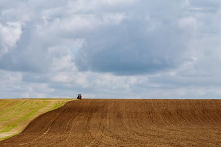 Farmer on a tractor plows the land with a seedbed cultivator