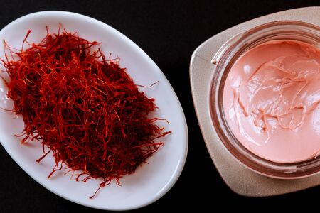 Saffron in a white plate and cosmetic cream on a black background. Cream with saffron extracts.