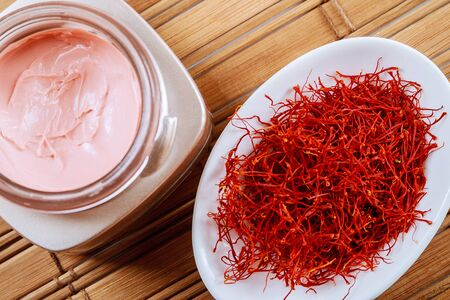 Saffron in a white plate and cosmetic cream on a wooden background. Cream with saffron extracts.