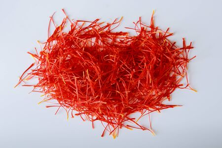 Heart-shaped saffron threads on a white background. Preparation of saffron threads for drying before use in cooking, cosmetology or medicine. Standard-Bild