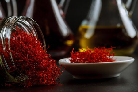 Dried saffron threads in a glass bottle and oil extract on a black background. The use of saffron in cooking, medicine, cosmetology.