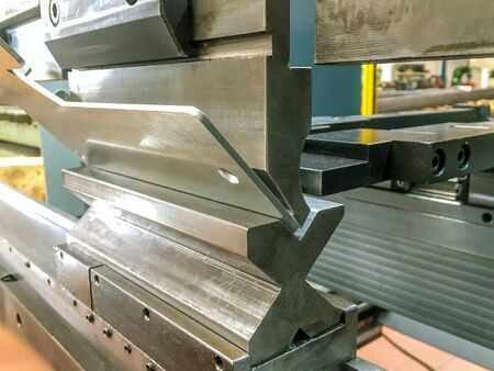 Bending sheet metal with a hydraulic bending machine at the factory. Archivio Fotografico