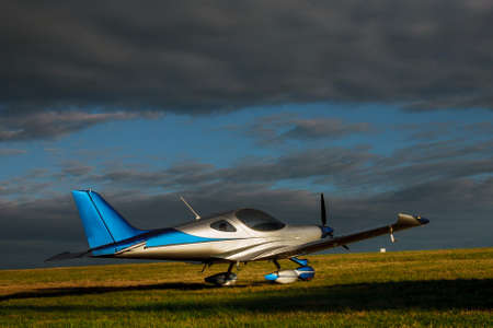 Light small plane on a grass field on a background of blue clouds