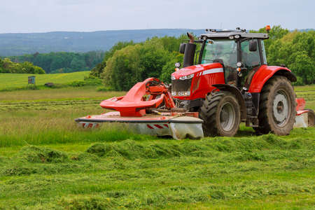 A big red tractor with two mowers mows the green grass on a silo. Banque d'images