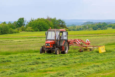Skutech, Czech Republic, 4 June 2020: A tractor with a rotary rake rakes freshly cut grass for silage on a large field.