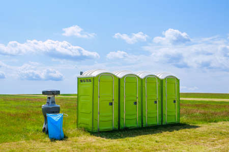 Portable toilet on the grass on a background of clouds. Archivio Fotografico