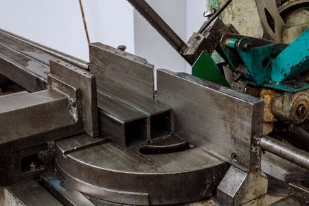Cutting steel profiles on a band saw in production.