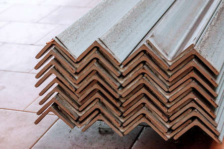 Rolled metal, L-profil. Stack of angle steel in the factory. Stock Photo