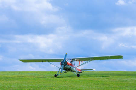 Small aircraft before takeoff on the field aginst blue sky