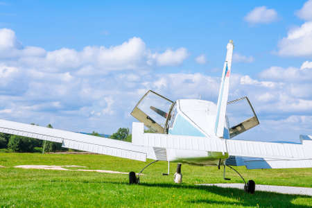 Small, 4-seater aircraft before takeoff on the field with open doors aginst blue sky
