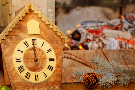 Retro clock with cuckoo with Roman numerals on the background of a fireplace with fire.