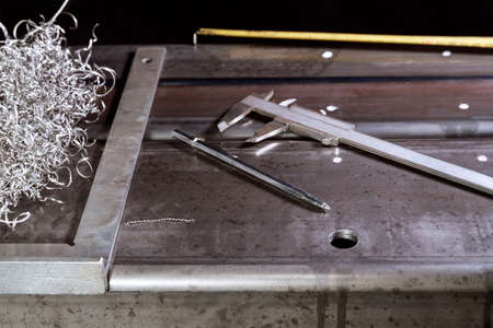 marking on a metal surface for drilling holes with a square and vernier calipers
