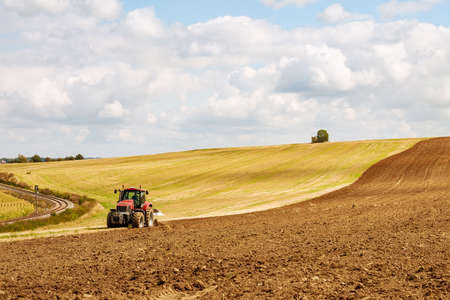 Farmer in red tractor preparing land for sowing