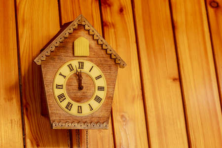 Cuckoo clock with Roman numerals on a wooden wall. Place for your text. Soon midnight