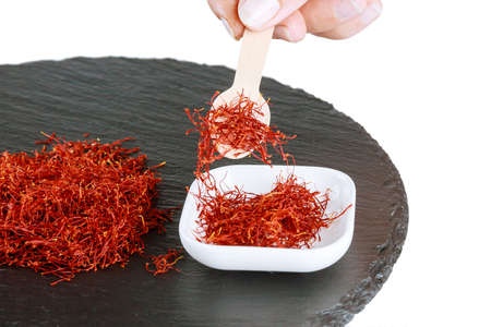 Pile of dry saffron threads on a black textured background. Spice. The use of saffron in medicine, cooking, cosmetology.