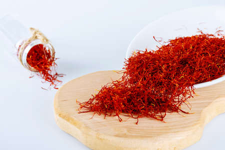 Dry Saffron Spice on a Plate on white Background. The use of saffron in cooking, medicine, cosmetology.