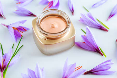 Saffron flowers on a white background and cosmetic cream with saffron extracts.